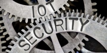 Macro photo of tooth wheel mechanism with IOT SECURITY letters imprinted on metal surface
